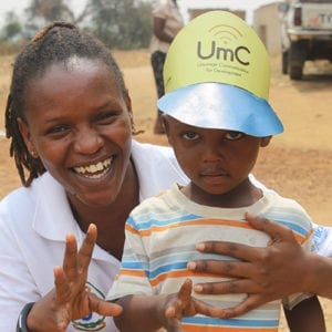 Mom and child wearing Umurage Communication for Development hat