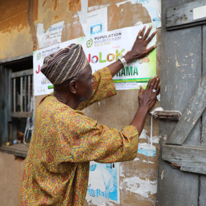 Man hangs up Jolokoto posters in Nigeria
