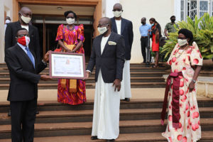 PMC-Uganda with Katikkiro Mayica receiving an award on steps outside the capital building.