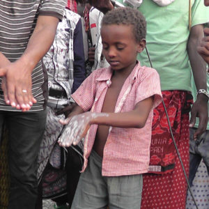 Young boy washing his hands at an event in Ethiopia