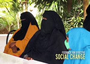 Three women sitting at a table out side. Graphic text reads: Feedback for effective social change