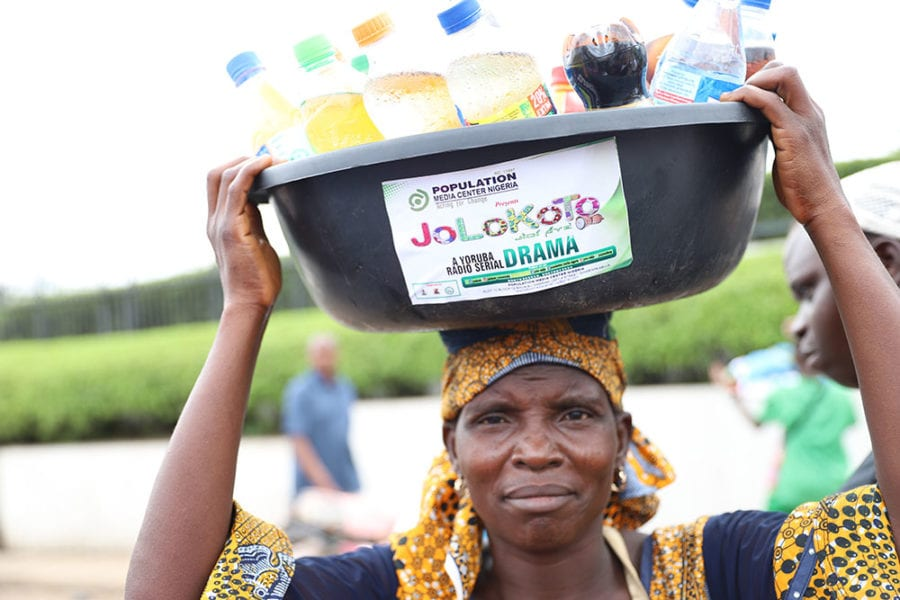 """woman carrying a bucket on her head filled with bottled soda drinks. The label on the bucket reads, """"Jolokoto."""""""