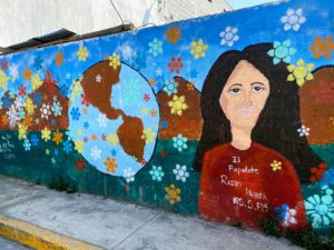 A wall on the side of the road covered in a mural painting. The mural features a woman with light skin and dark hair, a globe, and flowers.
