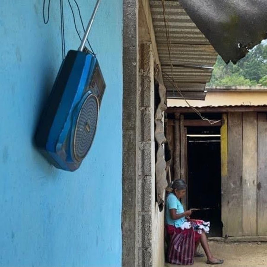 A woman sits in the background while the camera focuses on a radio hanging on a blue wall in the foreground.